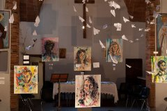 Exibition set during the gold swallow ceremony in 2016. The church was set up with Nadia's painting. Over them paper airplanes simbolizing Rondine's mission.
